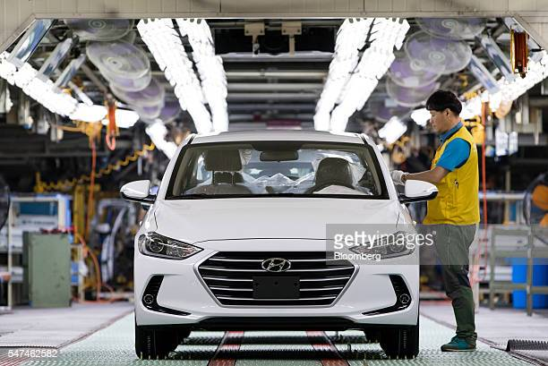 An employee performs final inspections on a Hyundai Motor Co. Elantra vehicle on the production line at the company's plant in Ulsan, South Korea, on...