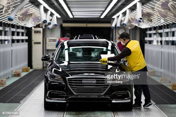 An employee performs final inspections on a Hyundai Motor Co. Genesis luxury sedan on the production line at the company's plant in Ulsan, South...