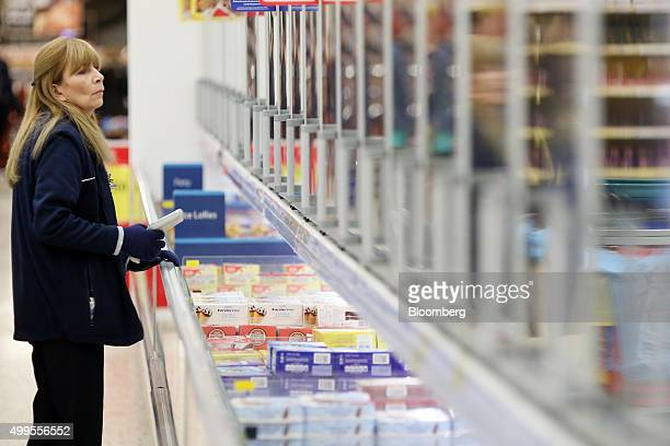 An employee picks shopping from the freezer section for home delivery at the Tesco Basildon Pitsea Extra supermarket operated by Tesco Plc in...