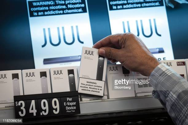 An employee picks up a Juul Labs Inc. Device kit for a customer at a store in San Francisco, California, U.S., on Wednesday, June 26, 2019. The city...