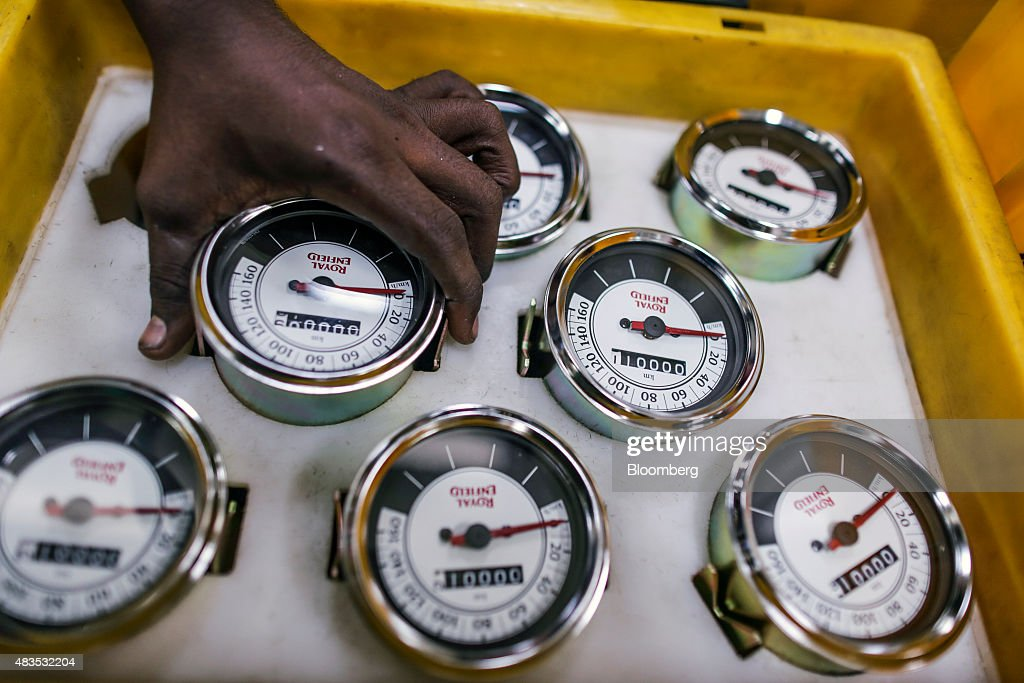 An employee picks up a speedometer for the Royal Enfield Motors Ltd Classic 350 motorcycle on the production line at the company`s manufacturing...