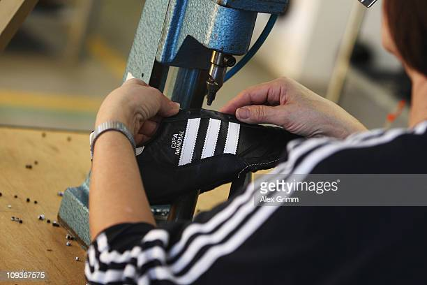 An employee pierces the shoelace holes for a handmade football boot at the factory of German sportinggoods maker Adidas AG on February 23 2011 in...