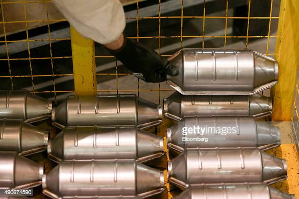 An employee places a automobile catalytic converter emission control device into a trolley at BM Catalysts in Mansfield UK on Wednesday Sept 30 2015...