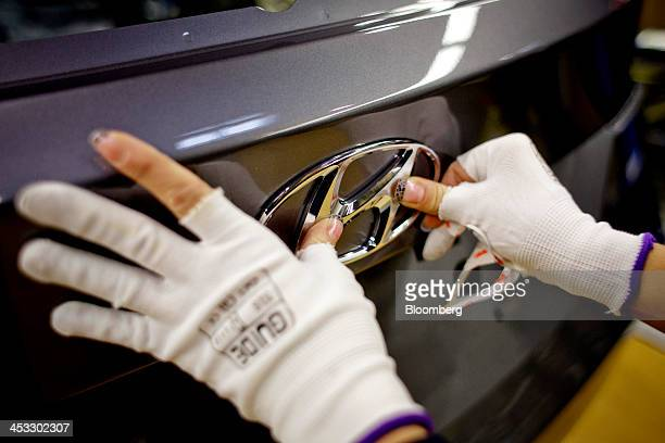 An employee places a badge onto the trunk of a Hyundai automobile during the final stages of manufacture at the Hyundai Motor Co plant in Nosovice...