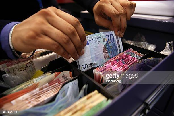 An employee places a bundle of twenty euro banknotes into a cashier's tray in this arranged photograph taken inside a Travelex store operated by...