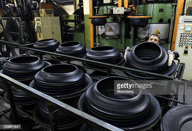 An employee places a car tire onto a rack at the ZAO Sibur Holding tire manufacturing plant in Voronezh, Russia, on Friday, Nov. 18, 2011. Pirelli is...