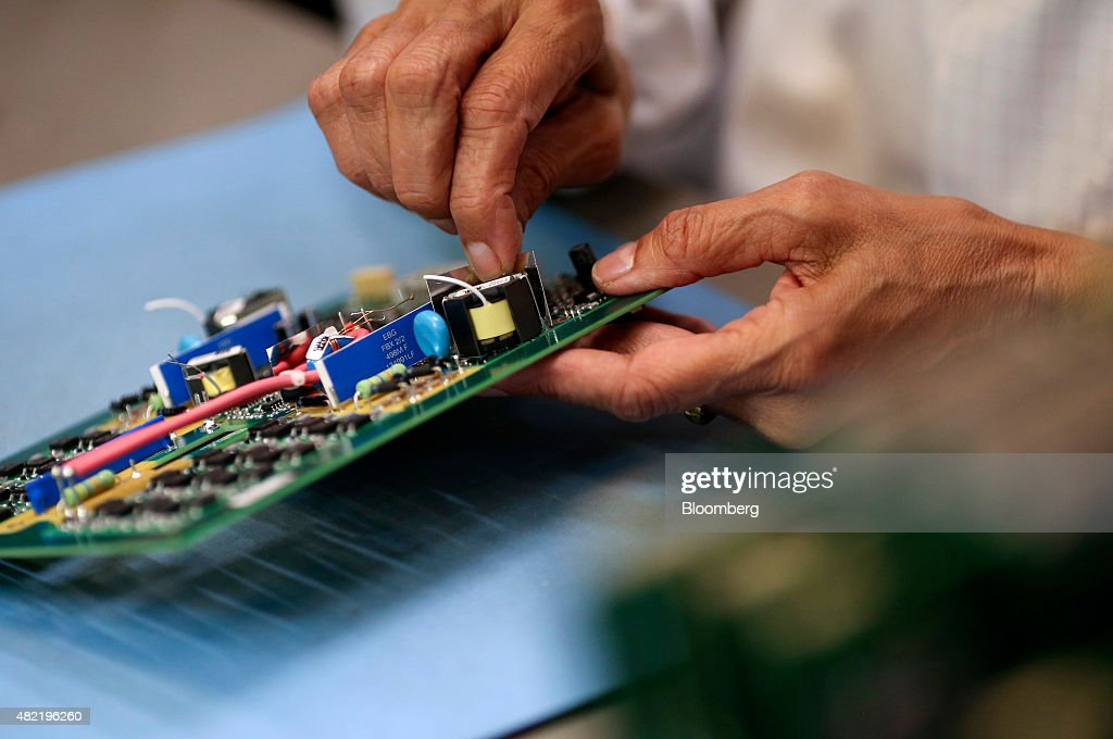An employee places a component onto a printed circuit board at Texcel Technology Plc's factory in Dartford, U.K., on Tuesday, July, 28, 2015. U.K. economic growth accelerated in the second quarter as business services and finance strengthened and North Sea output surged. Photographer: Chris Ratcliffe/Bloomberg via Getty Images