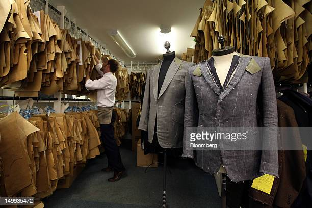 An employee places a customer's measurement template on to racking in the workshop at the Gieves Hawkes store owned by Trinity Ltd on Savile Row in...