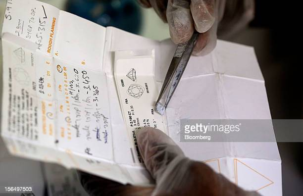 An employee places a cut diamond in its identification packet at the Shrenuj Botswana Ltd sightholder office in Gaborone Botswana on Thursday Oct 25...