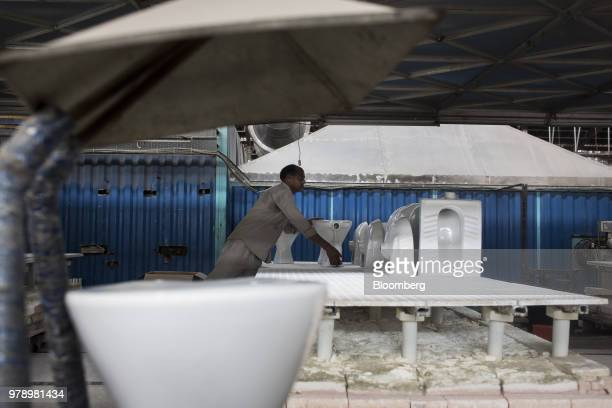 An employee places a glazed toilet bowl on a kiln platform truck at the HSIL Ltd factory in Bahadurgarh Haryana India on Monday June 11 2018 Indian...