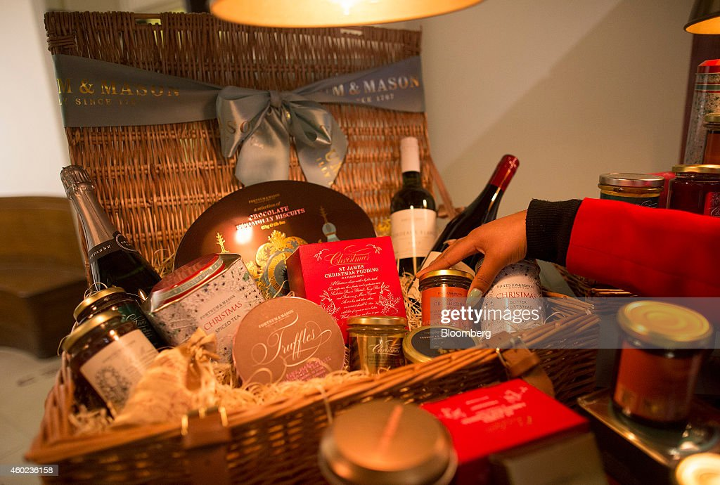 An employee places a jar of cranberry sauce into a festive food hamper inside a pop-up store, operated by Fortnum & Mason Plc, during a seasonal Christmas event at Somerset House in London, U.K., on Tuesday, Dec. 9, 2014. The British will be the biggest spenders in Europe on Christmas gifts this year, according to a study commissioned by Dutch bank ING Groep NV. Photographer: Simon Dawson/Bloomberg via Getty Images
