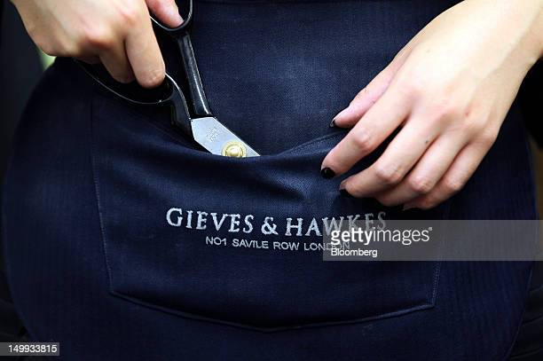 An employee places a pair of scissors in to a waist pouch at the Gieves Hawkes store owned by Trinity Ltd on Saville Row in London UK on Tuesday Aug...