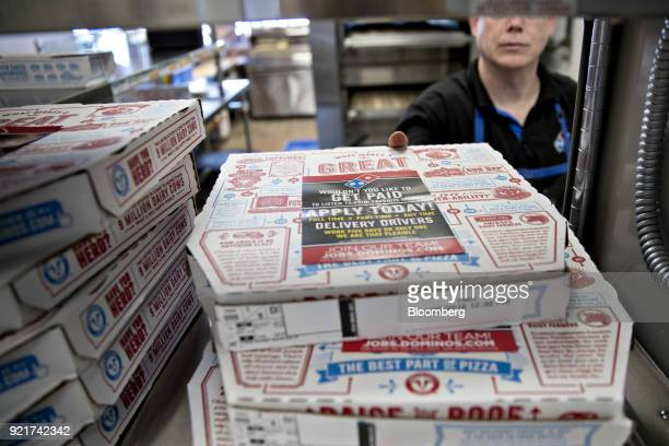 An employee places a pizza box onto a shelf at a Domino's Pizza Inc restaurant in Chantilly Virginia US on Tuesday Feb 20 2018 Domino's released...