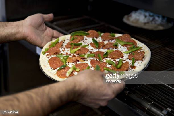 An employee places a pizza into an oven at a Domino's Pizza Inc restaurant in Chantilly Virginia US on Tuesday Feb 20 2018 Domino's released earnings...
