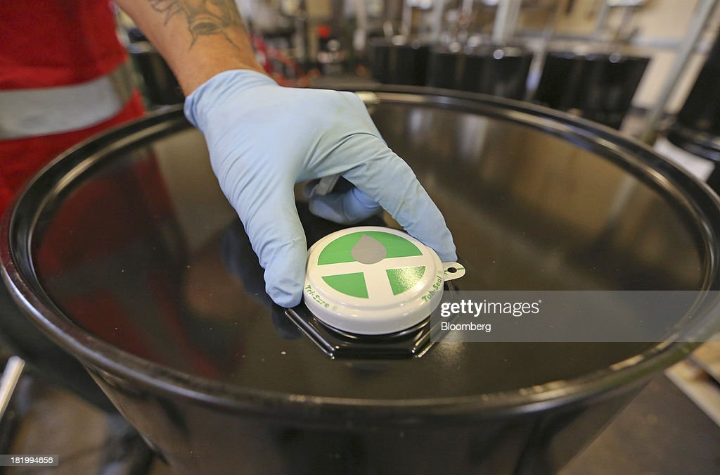 An employee places a seal on to a flavoring container drum at the Treatt Plc factory in Bury St Edmunds, U.K., on Wednesday, Sept. 25, 2013. Treatt Plc, the U.K. supplier of mango oil to the Body Shop, is considering the biggest investment splurge in its 127-year history as Chief Executive Officer Daemmon Reeve seeks to unshackle the company from family owned traditions. Photographer: Chris Ratcliffe/Bloomberg via Getty Images
