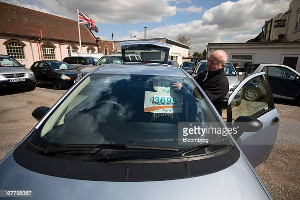 An employee places a sign advertising the price of a automobile on the sunvisor of a car at an independent secondhand dealership in LeighonSea UK on...