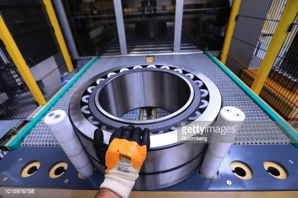 An employee places a steel roller bearing into a protective coating machine on the assembly line inside the Schaeffler AG factory in Schweinfurt...