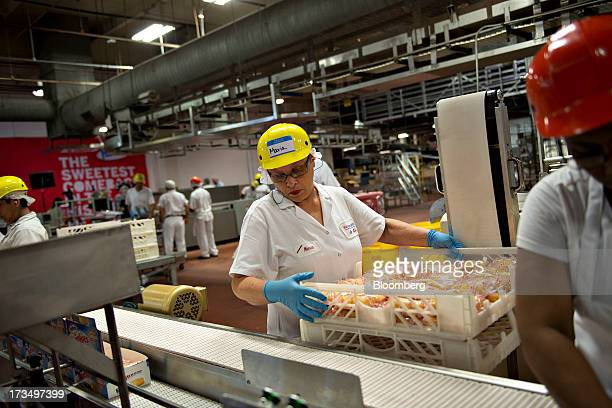 An employee places a tray of Hostess Brands LLC Twinkies snack cakes alongside a packaging line at the company's bakery in Schiller Park Illinois US...
