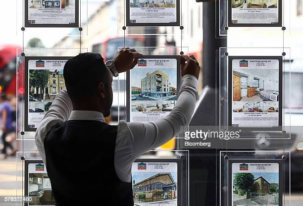 An employee places an advert for a residential house for sale into an estate agent's window in this arranged photograph in the Hackney borough of...
