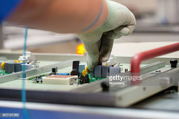 An employee places an electrical component onto a circuit board on the axial fan assembly line inside the Ebm Papst GmbH transportation ventilation...