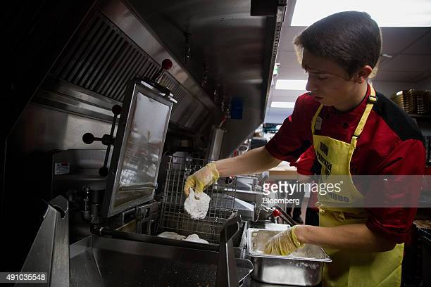 An employee places breaded chicken into a fryer to cook for guests during an event ahead of the grand opening for a ChickfilA restaurant in New York...