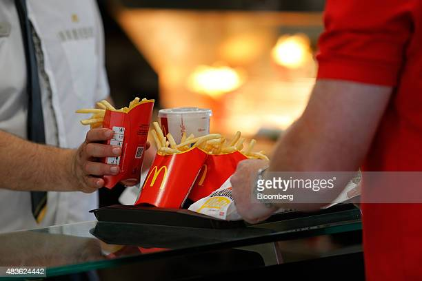 An employee places cartons of fries onto a customer's tray inside a McDonald's Corp restaurant in Manchester UK on Monday Aug 10 2015 McDonald's...