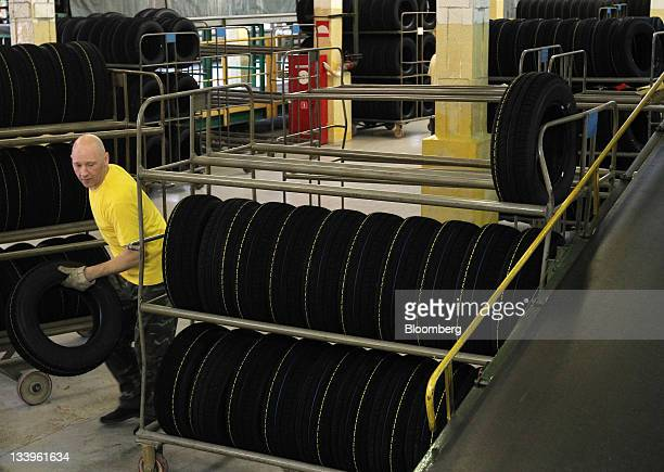 An employee places completed car tires onto a rack at the ZAO Sibur Holding tire manufacturing plant in Voronezh, Russia, on Friday, Nov. 18, 2011....