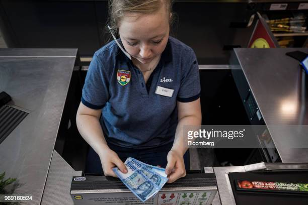 An employee places Hungarian one thousand forint currency banknotes into the cash register at the checkout area inside a Lidl Ltd grocery store in...