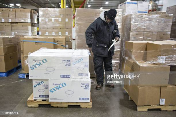 An employee places inventory tags on boxes of Sysco Corp plastic bowls at the company's distribution facility in Des Plaines Illinois US on Tuesday...