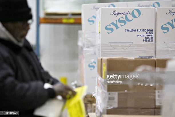 An employee places inventory tags on boxes Sysco Corp plastic bowls at the company's distribution facility in Des Plaines Illinois US on Tuesday Jan...