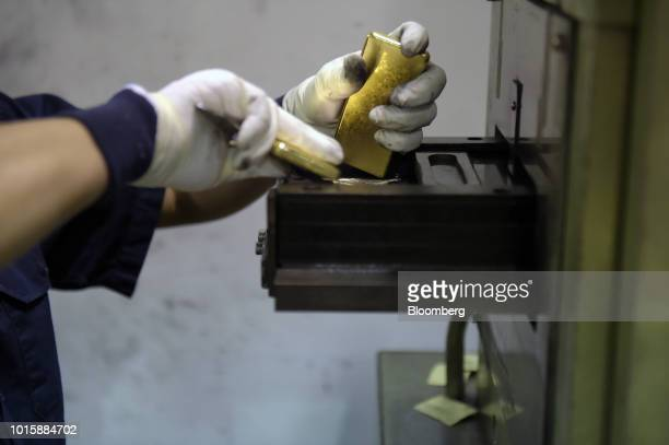 An employee places one kilogram gold bars into a stamp at the Perth Mint Refinery operated by Gold Corp in Perth Australia on Thursday Aug 9 2018...