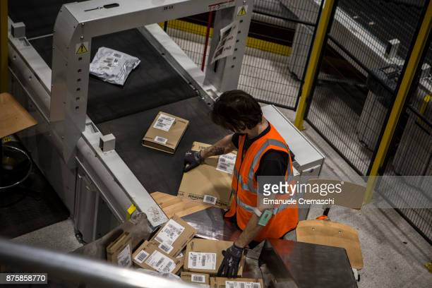 An employee places parcels on a conveyor belt at the Amazoncom MPX5 fulfillment center on November 17 2017 in Castel San Giovanni Italy Established...