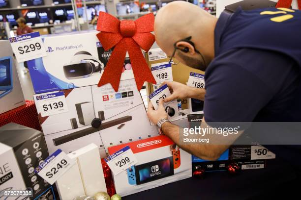 An employee places price tags on Black Friday sale items displayed for the media at a WalMart Stores Inc location in Burbank California US on...
