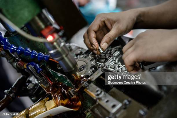 an employee places self-clinching fasteners in a machine at a manufacturing facility - shah alam stock photos and pictures