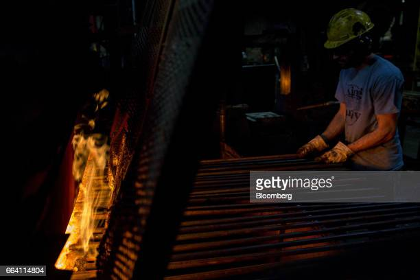 An employee places steel rods in a furnace as tools are forged at the Vaughan Bushnell Manufacturing Co facility in Bushnell Illinois US on Friday...