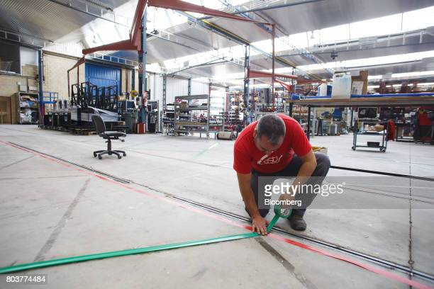An employee places tape to make a route for tracking by mobile robots also known as an AGV or automated guided vehicles inside the Automatismos y...