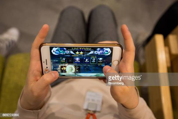 An employee plays the Netmarble Games Corp. Seven Knights mobile role-playing game on a smartphone in the cafeteria at the company's headquarters in...