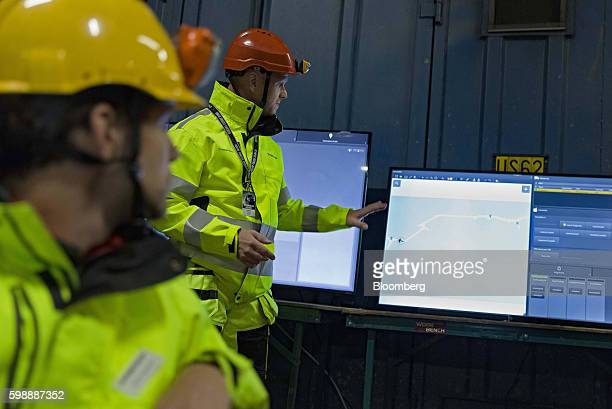 An employee points to a computer screen displaying part of the operational route of a Volvo Autonomous FMX selfdriving truck manufactured by Volvo...