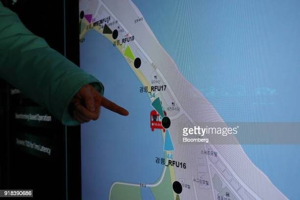 An employee points to a map displayed on a screen onboard an autonomous 5G connected bus operated by KT Corp during a media event in Gangneung...