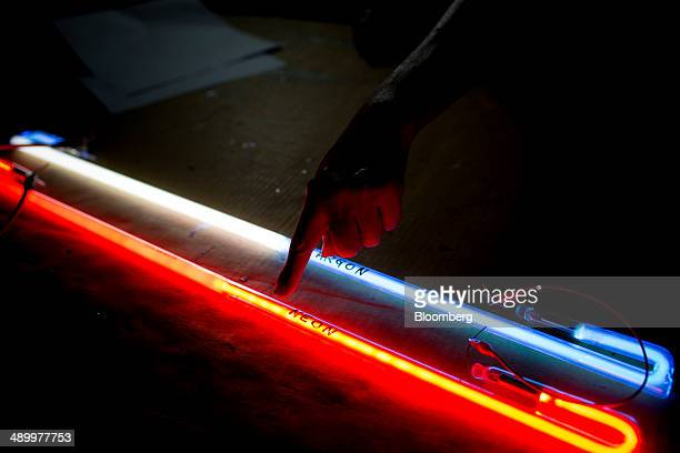 An employee points to a neon light bottom sitting next to an argon light at Nam Wah Neonlight Electrical Mfy Ltd in Hong Kong China on Monday April...