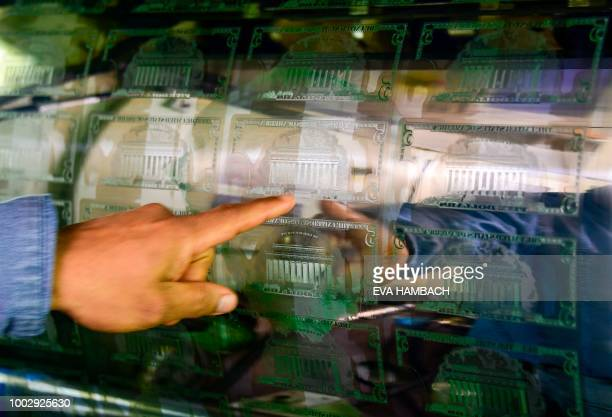 An employee points to the inked printing plate of a sheet of 5 USD notes at the US Treasury's Bureau of Engraving and Printing in Washington DC July...