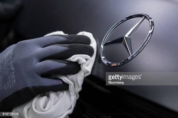 An employee polishes a badge on a MercedesBenz AG AMG GT high performance luxury automobile on the assembly line at the automaker's plant in...