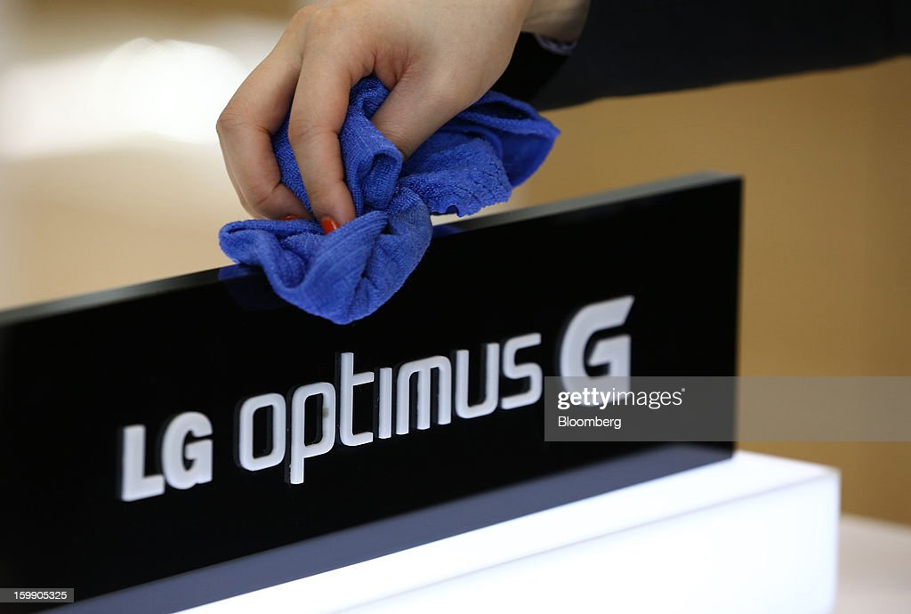 An employee polishes a sign for LG Electronics Inc.'s Optimus G smartphone at the company's flagship store in Seoul, South Korea, on Tuesday, Jan. 22, 2013. LG Electronics Inc. is scheduled to release fourth-quarter earnings on Jan. 30. Photographer: SeongJoon Cho/Bloomberg via Getty Images