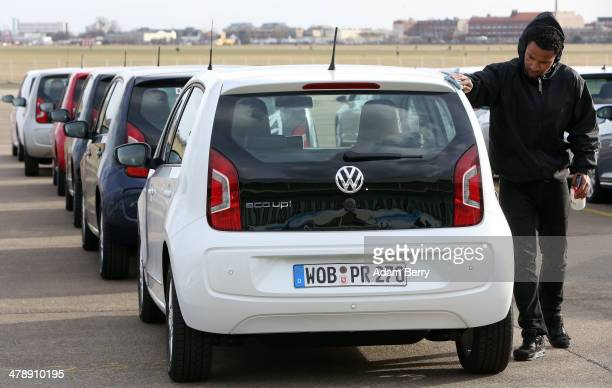 An employee polishes a Volkswagen eco up! automobile at the Electric Mobility Week , a public Volkswagen event at the former Tempelhof airport, on...