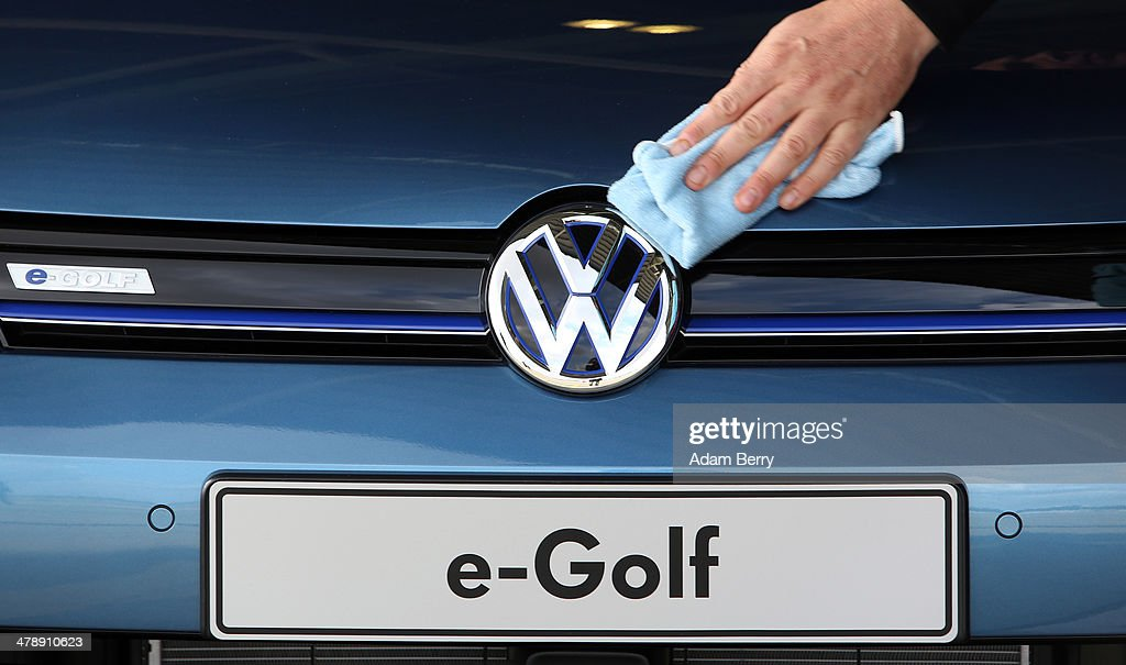 An employee polishes an e-Golf electric automobile at the Electric Mobility Week (e-Mobilitaetswochen), a public Volkswagen (VW) event at the former Tempelhof airport, on March 15, 2014 in Berlin, Germany. The event was designed to promote the company's e-Golf und e-up! automobiles, as well as its other alternative energy powered vehicles.