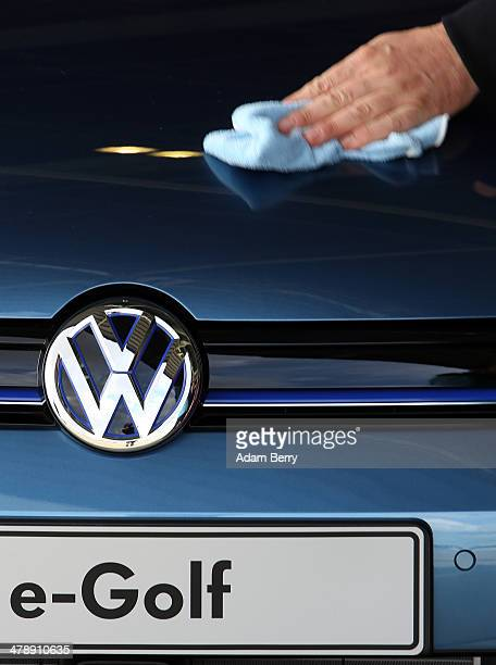 An employee polishes an e-Golf electric automobile at the Electric Mobility Week , a public Volkswagen event at the former Tempelhof airport, on...