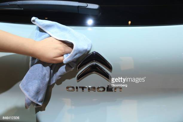 An employee polishes the badge of a Citroen C3 Aircross automobile manufactured by PSA Peugeot Citroen during the second media preview day of the IAA...