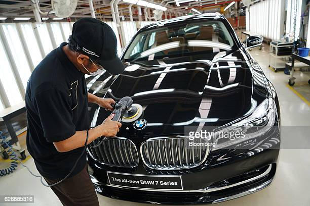 An employee polishes the hood of a BMW AG 7Series sedan at the assembly line of a PT Gaya Motor factory in Jakarta Indonesia on Wednesday Nov 30 2016...