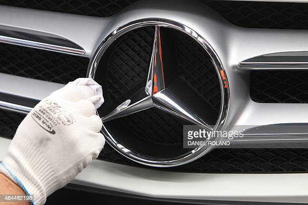 An employee polishes the logo of a mercedes car at the MercedesBenz factory in Rastatt Germany on August 19 2015 AFP PHOTO / DANIEL ROLAND