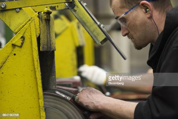 An employee polishes the metal on a pocket knife at the WR Case Sons Cutlery Co manufacturing facility in Bradford Pennsylvania US on Wednesday March...